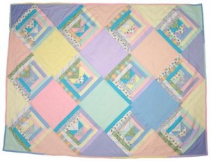 Shows a baby quilt in bright pastel colours