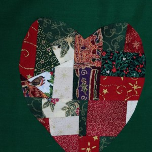 A heart shape on the green bag showing images of holly and other Christmas images.