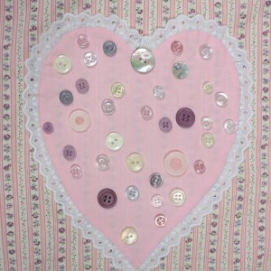 A pink appliqué heart on a pink patchwork shopping bag project with pretty buttons.