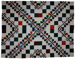Shows the patchwork quilt know as All Square.  This uses a light coloured background on which many many small sqaures, mainly green, are used to make a pleasing geometric pattern.