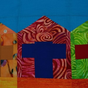 A detail of the beach huts patchwork wall-hanging showing one hut. It is mostly dark red with a blue doorway.