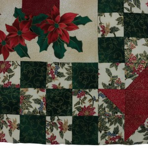 A detail of the candles wallhanging showing the bottom right hand corner of the center panel. The holly sprays are visible here.