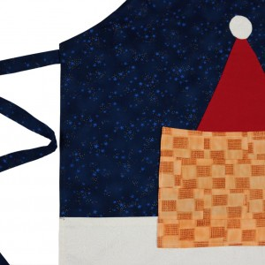 A detail of the christmas patchwork apron showing the main components , which are the blue and white panels, the red santa hat and the patch pocket.