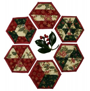 A set of six Christmas coasters arranged around a sprig of holly.
