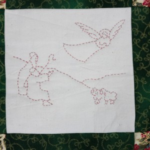 One of four quilted panels on the Christmas wall-hanging. An Angel appears before the Shepherds.