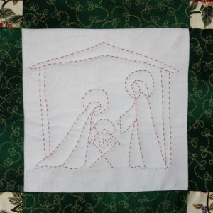 One of four quilted panels on the Christmas wall-hanging. Lying in a manger.