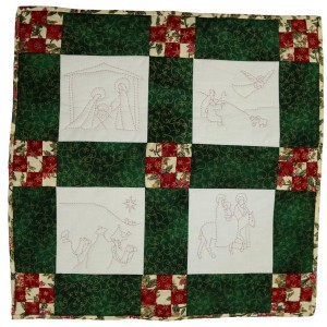 A Christmas wall-hanging which has four quilted panles all showing scenes from the story of Christmas.