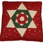 The folded star cushion cover. The main colour is red which forms the bacground. the start is formed using a cream colour and the detail is picked out in green and red. Gold details appear on the fabric.