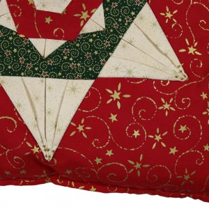 A detail showing one corner, and two points of the six pointed star on the folded star cushion cover.