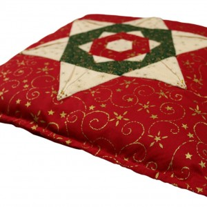 Shows the finished folded star cushion cover in place on a cushion.