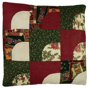 Shows the jockeys cap cushion cover in traditional Christmas colours; Green, red and gold. The cushiois made from nine square panels in a 3 x 3 arrangement.