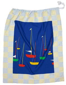 A photograph of a drawstring laundry bag with a pale blue and yellow patchwork background and a cheerful yachts-at-sea print