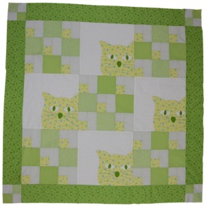 This is a brightly coloured quilt in shades of bright green which features the face of a really cute cat.