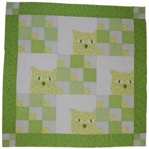 This shows a quilt project suitable for making for a baby.  The main colors are bright green and it features a happy quilted cat.