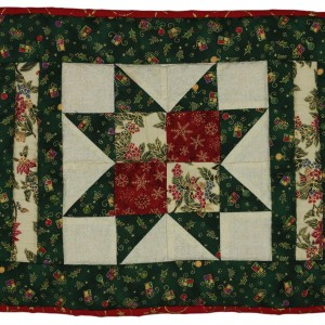 A variation on the sawtooth star pattern this time on a square tablemat. it is predominantly green with red and gold details.