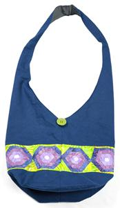 A patchwork shoulder bag in blue with light green, blue and purple details.  A light green button adds interest and gives sparkle to the design.