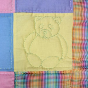 A detail of the squares and bears quilt showing one quilted panel which contains a bear.