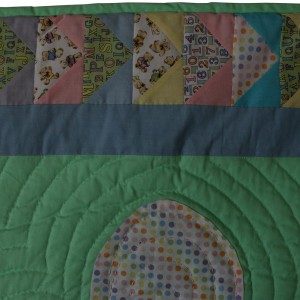 A detail of the border, some of the bacgrount quilting and part of a quilted ballon on the baby quilt balloons.