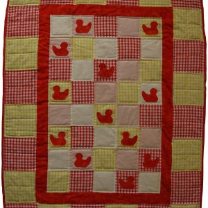 The full cheerful ducklings baby quilt in red and yellow. Red ducks appear next to bright gingham.