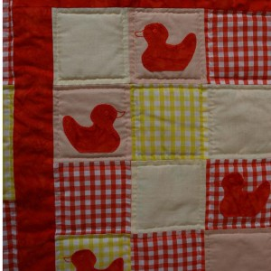 A detail of the ducklings quilt showing four of the red ducklings.