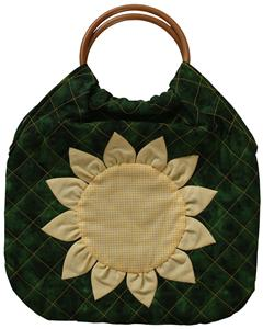 A green quilted bag with a large yellow appliquéd sunflower.  The handles are made from attractive wooden hoops.