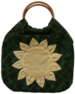 A useful and elegant quilted bag in green and yellow with wooden handles.