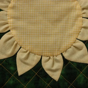 A straight-on view of part of the sunflower bag, where the appliqued sun is fixed to the quilted section.