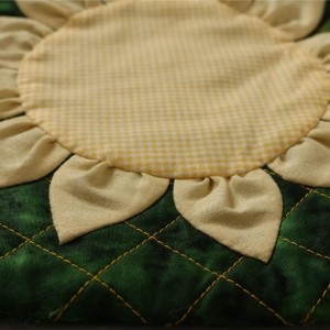 A perspective view of the quilted sunflower bag showing the area where the appliqued sunflower is fixed to the quilted bag. The stitching is yellow and the dominant colour on the bag is green.